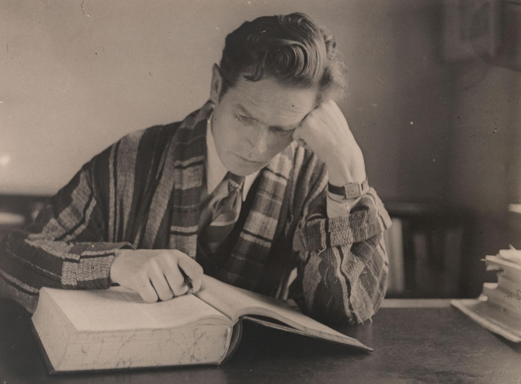 Juhani Konkka lukee kirjaa pöydän ääressä. SKS KIA, Juhani Konkan arkisto. CC BY 4.0
