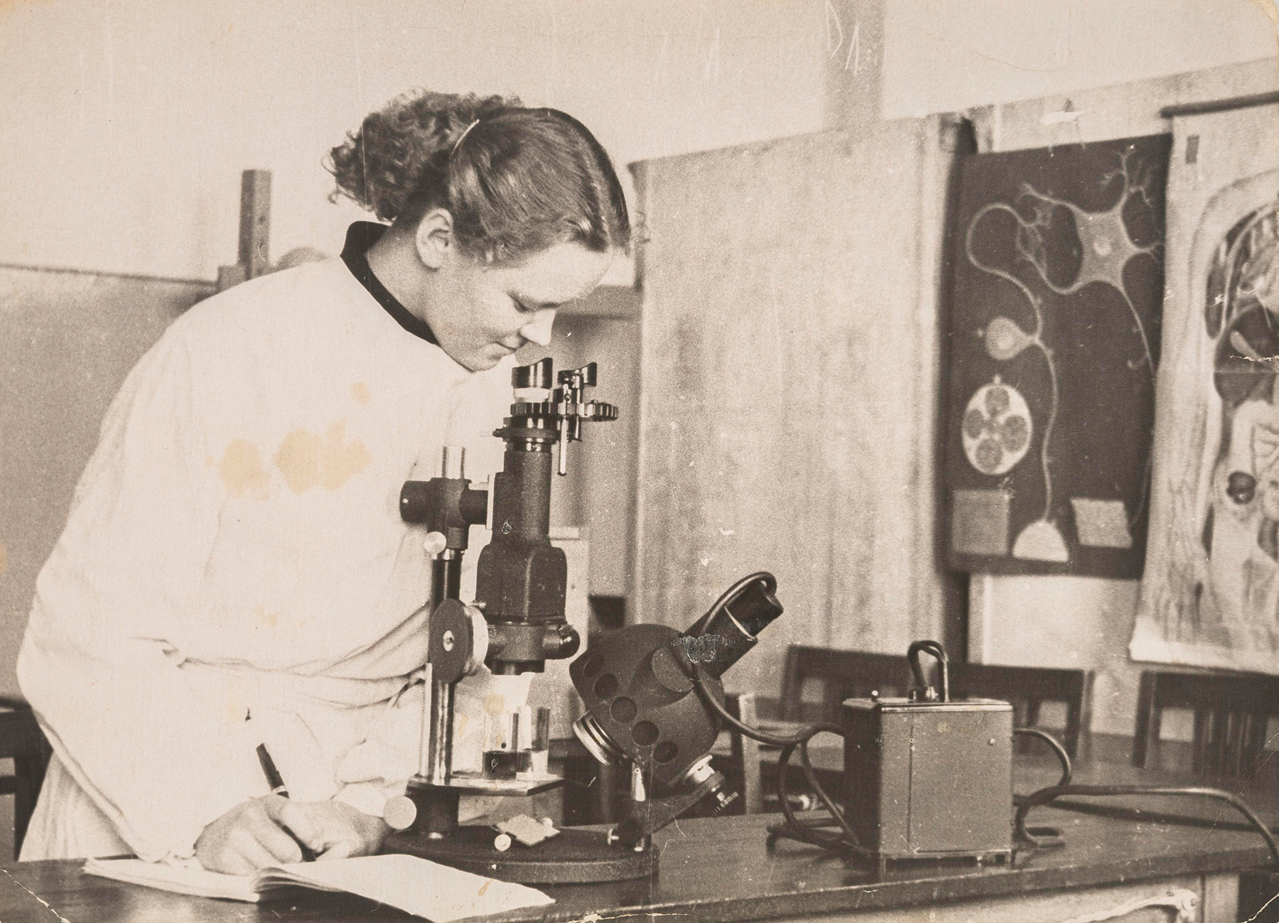 Viola Heistonen työskentelemässä mikroskoopilla fysiologian oppitunnilla Arkangelissa vuonna 1957. SKS KIA, Heistonen-suvun arkisto. CC BY 4.0