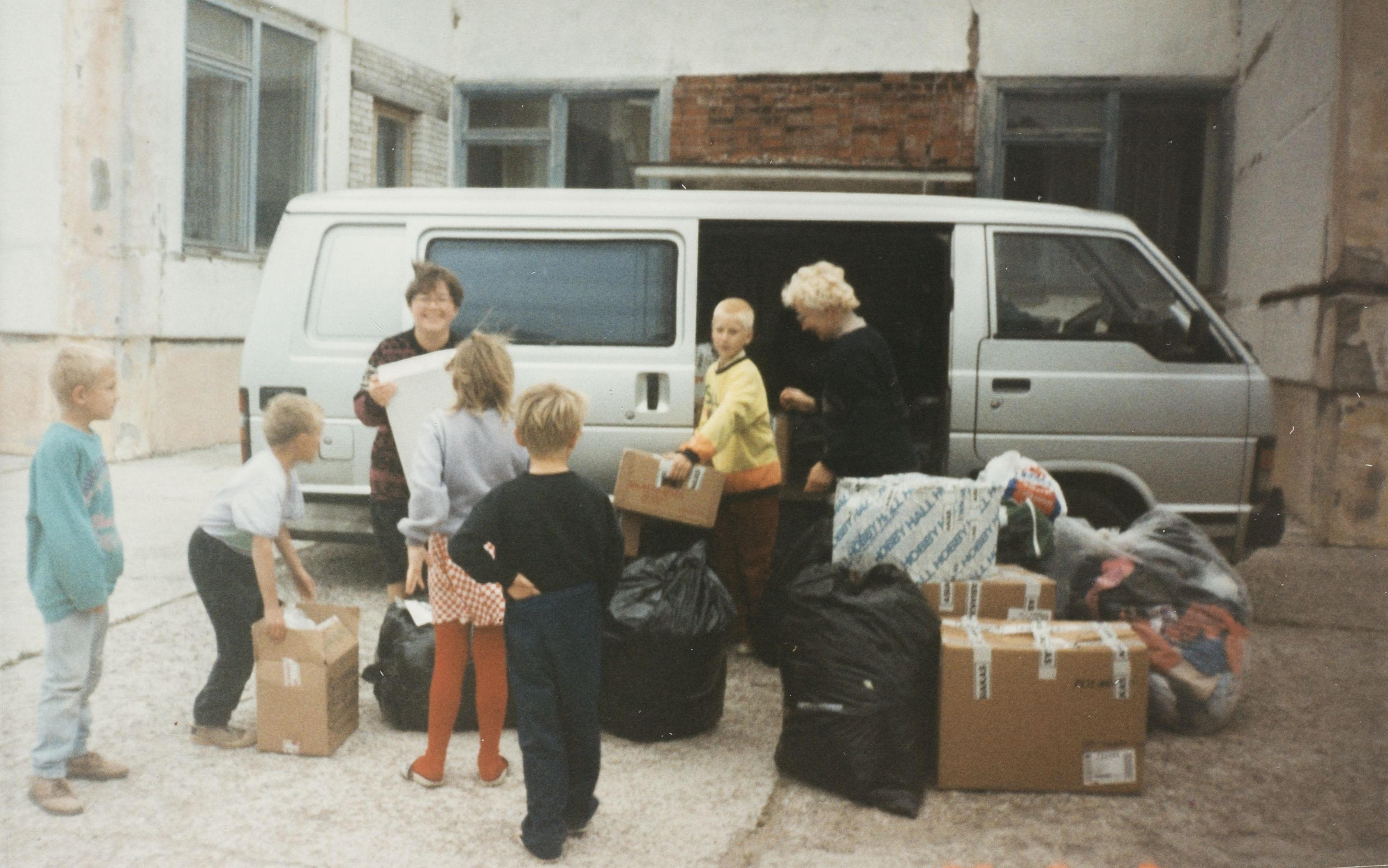 Lilja Skibjuk (o.s. Tatti) toimittamassa tavara-apua venäläiseen lastenkotiin vuonna 1996. Avustusta vastaanottamassa ovat lastenkodin johtaja ja lapsia. SKS KIA, Tatti-perheen arkisto. CC BY 4.0
