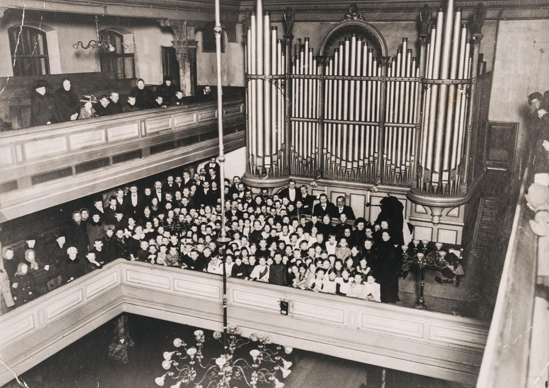 Pietarin suomalaisen seurakunnan kirkko  ennen vuoden 1917 vallankumousta. Mooses Putro kuorolaisten takana urkujen ääressä. SKS KIA, Putro-suvun arkisto. CC BY 4.0