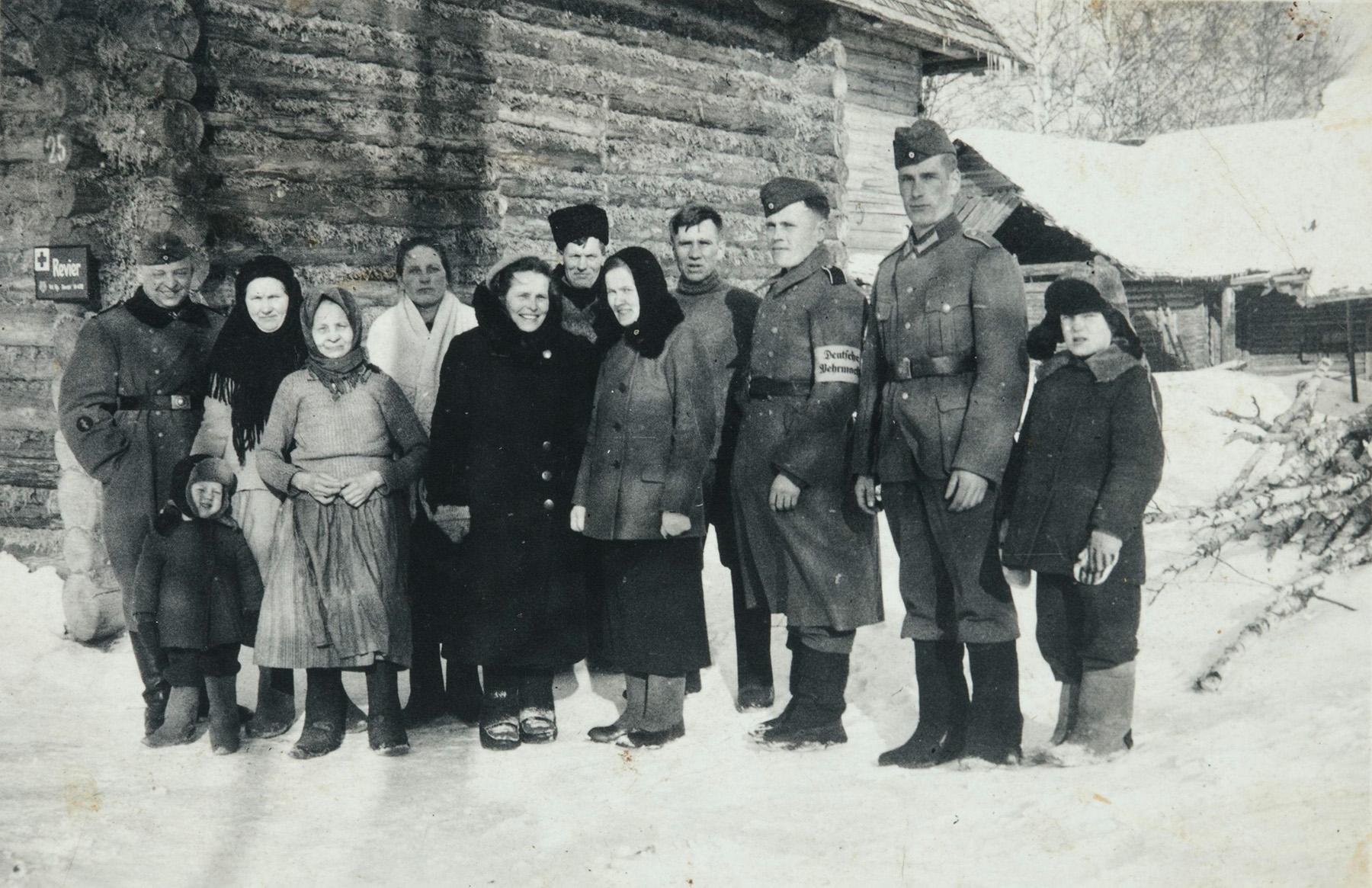 Saksalaiset ottivat Peuhkurin perheen kotitalon käyttöönsä miehityksen. Kuvassa saksalaisia sotilaita ja Peuhkurin perhettä ja naapuri. Kuva on saksalaisen sotilaan ottama, 1940-luku. SKS:n arkisto, Peuhkuri-perheen arkisto. CC BY 4.0