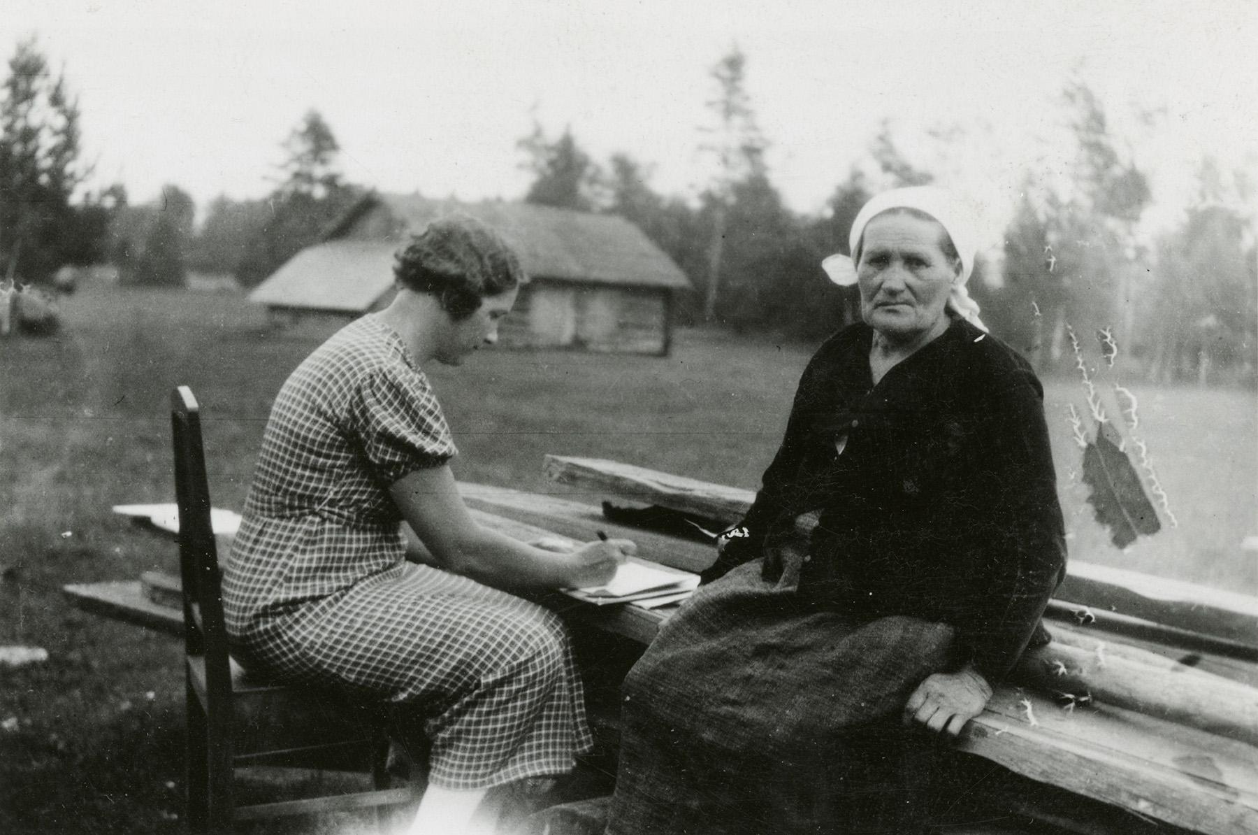 Kansanrunoudentutkija Elsa Enäjärvi-Haavio kirjoittaa perinnettä muistiin vuonna 1936. Haastateltavana hänellä on inkerikko Anna Kivisoo. Kuva SKS KRA, Topografinen kuvakokoelma. CC BY 4.0