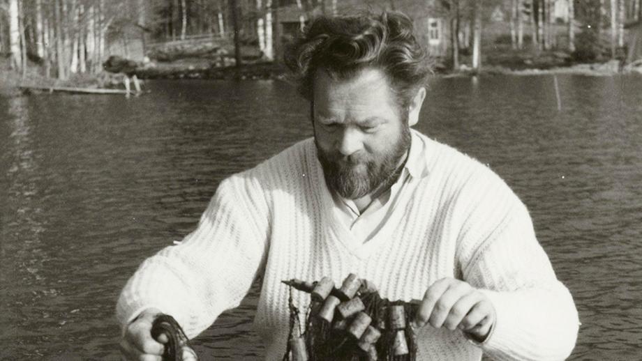 Juhani Konkka istuu veneessä, käsissään kalaverkot täynnä saalista. SKS KIA, Juhani Konkan arkisto. CC BY 4.0
