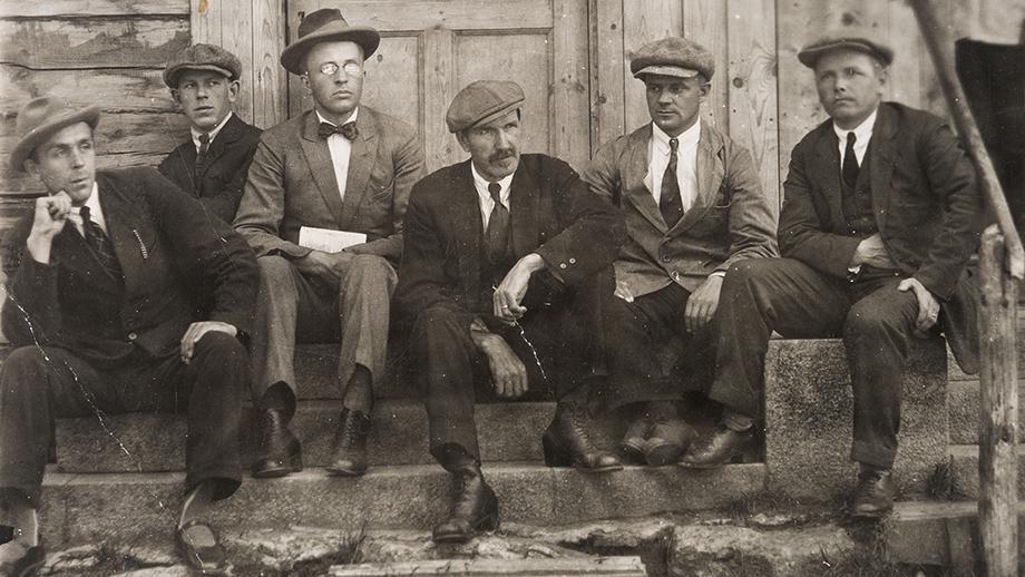Inkerinsuomalaisia miehiä istumassa portailla, keskellä Kaapre Tynni. Kuva Antti Hämäläinen. SKS KIA, Aale Tynnin arkisto. CC BY 4.0