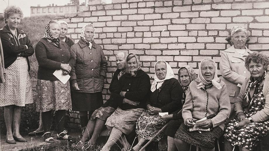 Ryhmä inkerinsuomalaisia naisia istuu tauolla tiiliaidan edessä talkoopäivänä. SKS KIA, Albert Kirjasen arkisto. CC BY 4.0