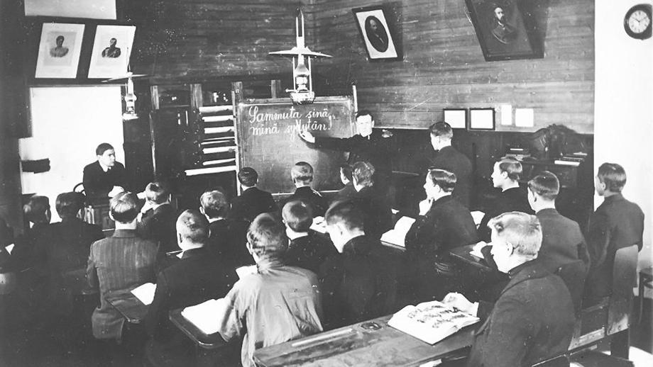 """Suomentunti Kolppanan seminaarissa vuonna 1916. """"Sammuta sinä, minä sytytän"""". Taululla Matti Virolainen. Inkeriläisten sivistyssäätiön kuvakokoelma, kuva 559. CC BY 4.0"""