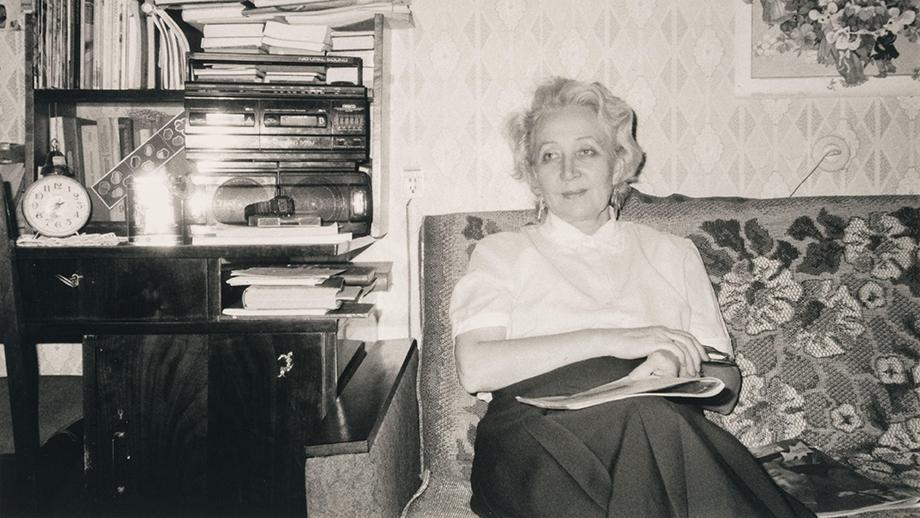 Kuva Lilja Skibjukista (o.s. Tatti) istumassa sohvalla lehti kädessään. SKS KIA, Tatti-perheen arkisto. CC BY 4.0