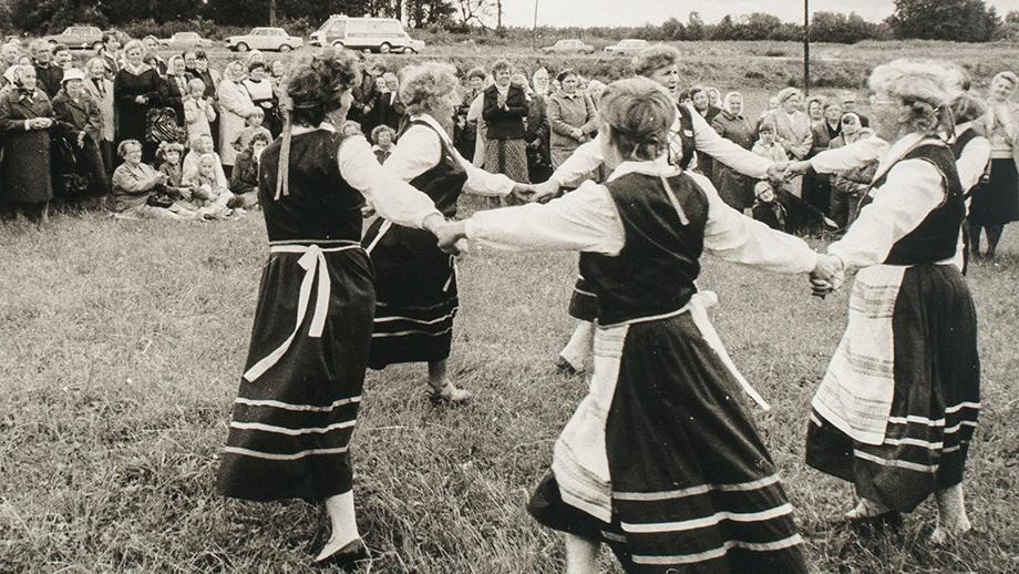 Tanssiesitys inkeriläisten kesäjuhlilla, taustalla näkyy Skuoritsan kirkon raunio. Kuvaaja Slava Väisänen, Skuoritsa, kesä 1990. SKS KIA, Malkki-perheen arkisto. CC BY 4.0